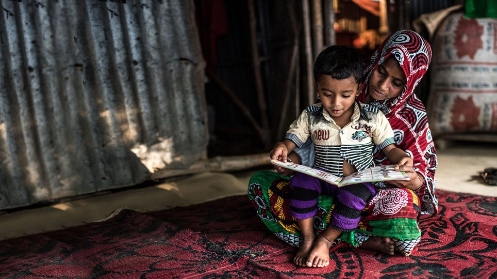 Four-year-old Arman sits on his mother's lap while they read a book.