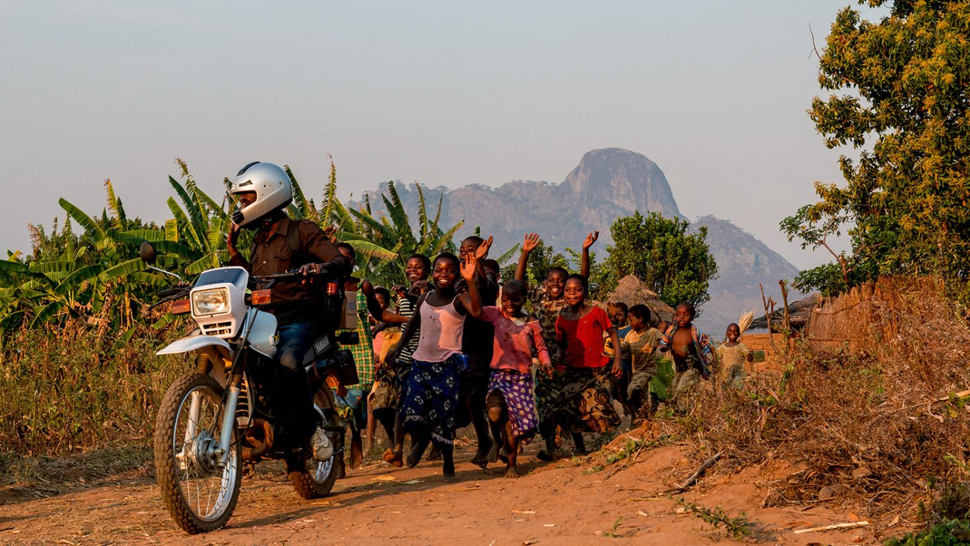 Madalitso Nyangulu riding his motorbike with lots of happy children running behind.