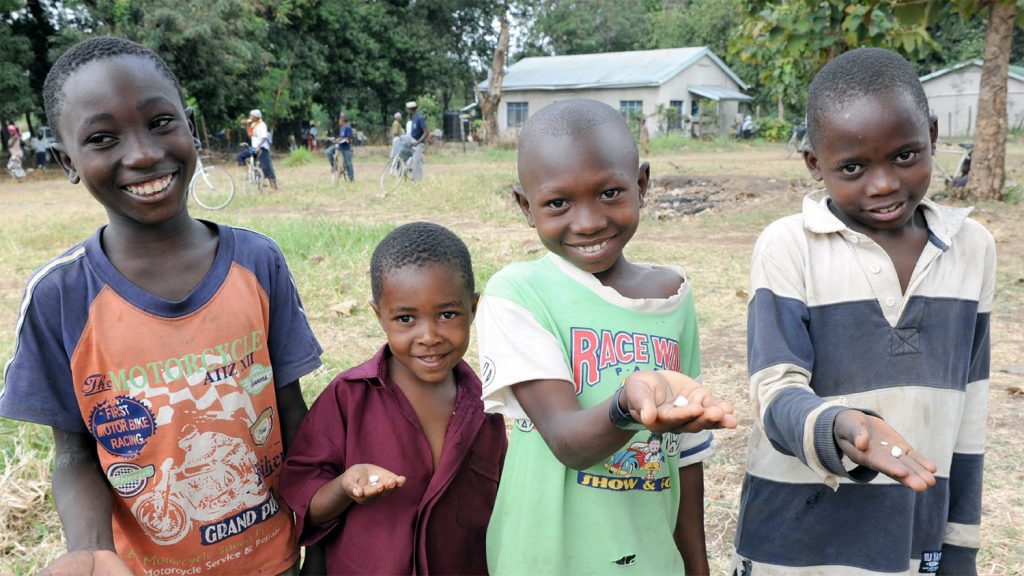 Children in Cameroon hold tablets that they will take to prevent the spread of diseases such as trachoma.