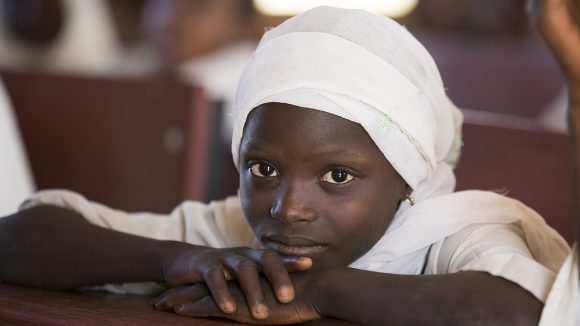 Seven-year-old Dorcas from Nigeria sits with her chin on her hands and looks at the camera.