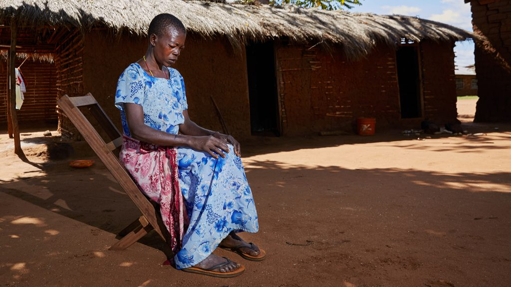Fatuma sits quietly on a chair outside her home. Her eyes look sore and swollen.