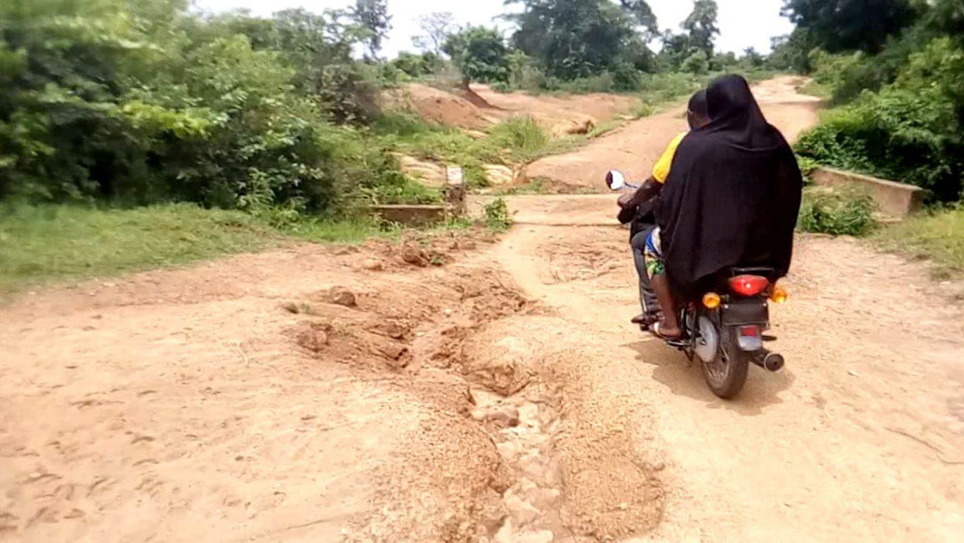 Two eye health workers ride through a remote region in Nigeria.