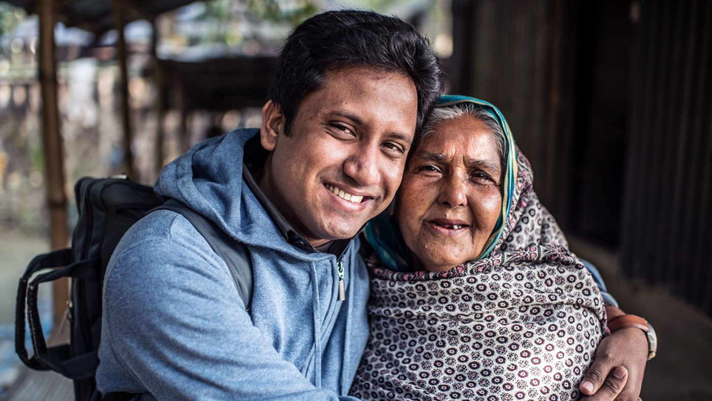 Cataract patient Kulsum smiles and embraces Sightsavers' staff member Mosheur.