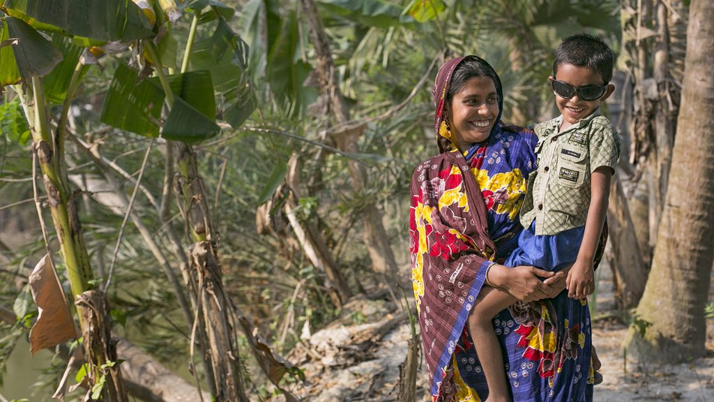 A woman holds her smiling son as they walk through a wooded area near their village.