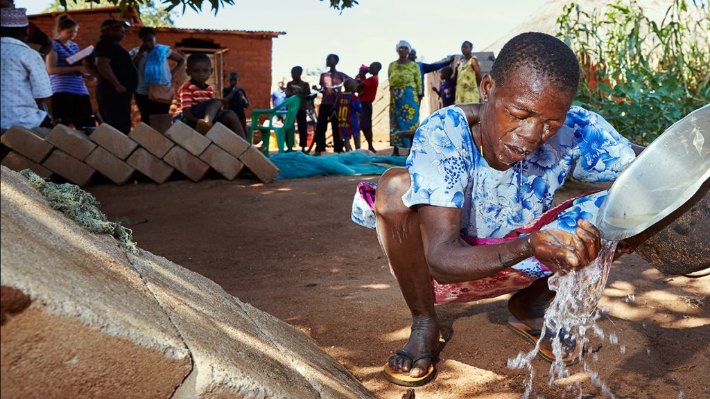 A woman in Tanzania splashes water on her face from a metal bucket.