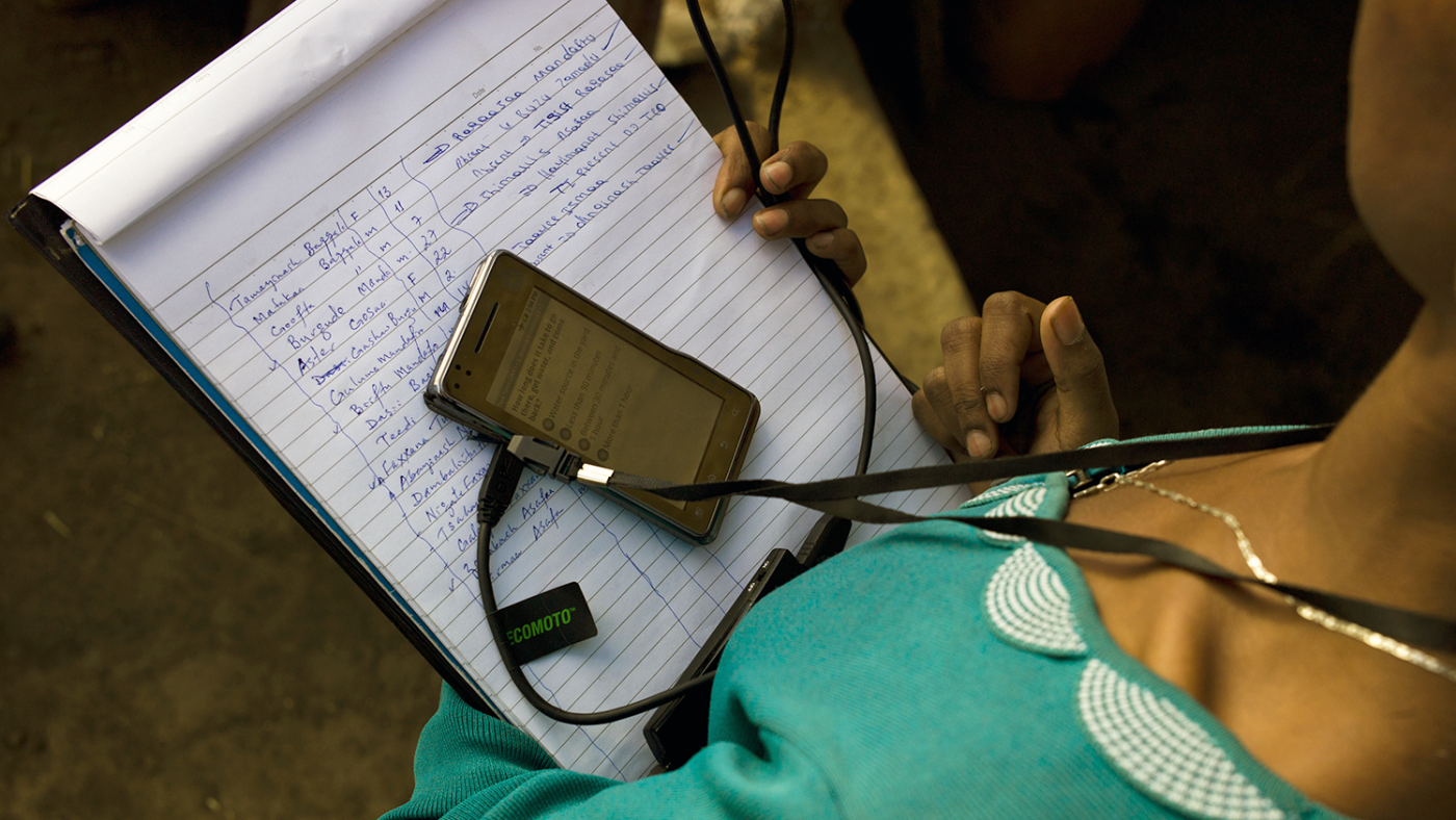 An eye care worker holding a notepad with a phone resting on top.