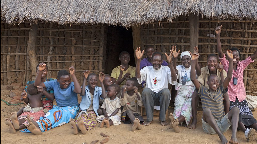 Winesi smiles with his family outside their home in Malawi.