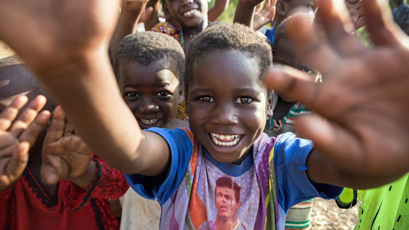 Two smiling children from the Yendi district in Ghana wave their hands in the air.