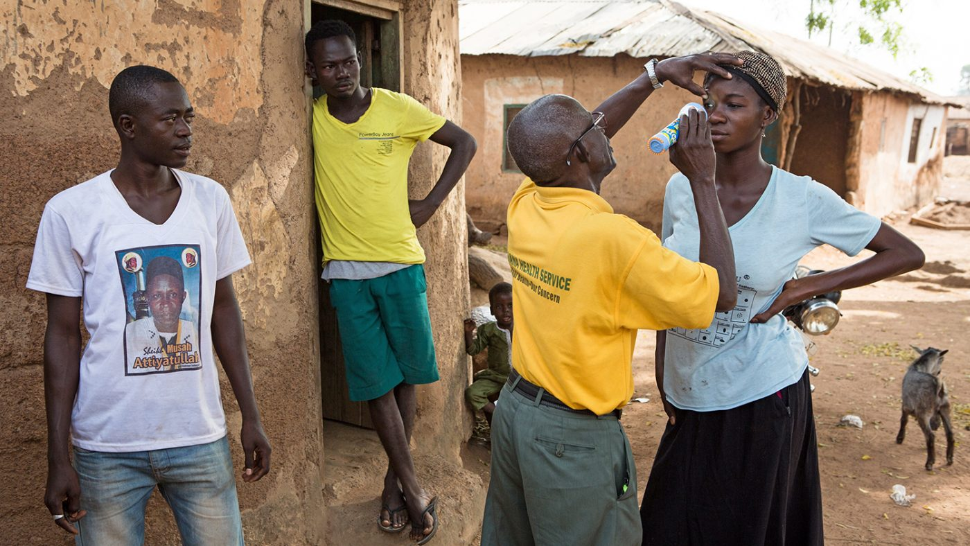 A woman in Ghana has her eyes checked for trachoma while her neighbours look on.