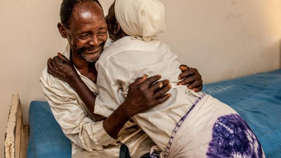 Winesi a 69 year old man, hugs his wife and smiles after his cataract operation.