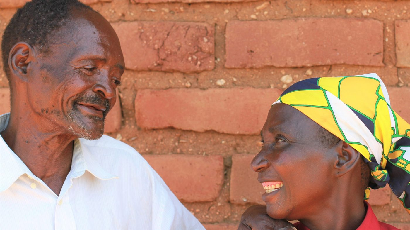 Winesi and his wife smiling at each other.