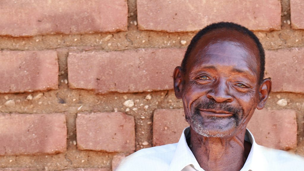 Winesi outside his home in Malawi.