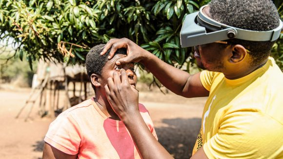 A man in a Sightsavers tshirt examining a lady's eyes for trachoma.