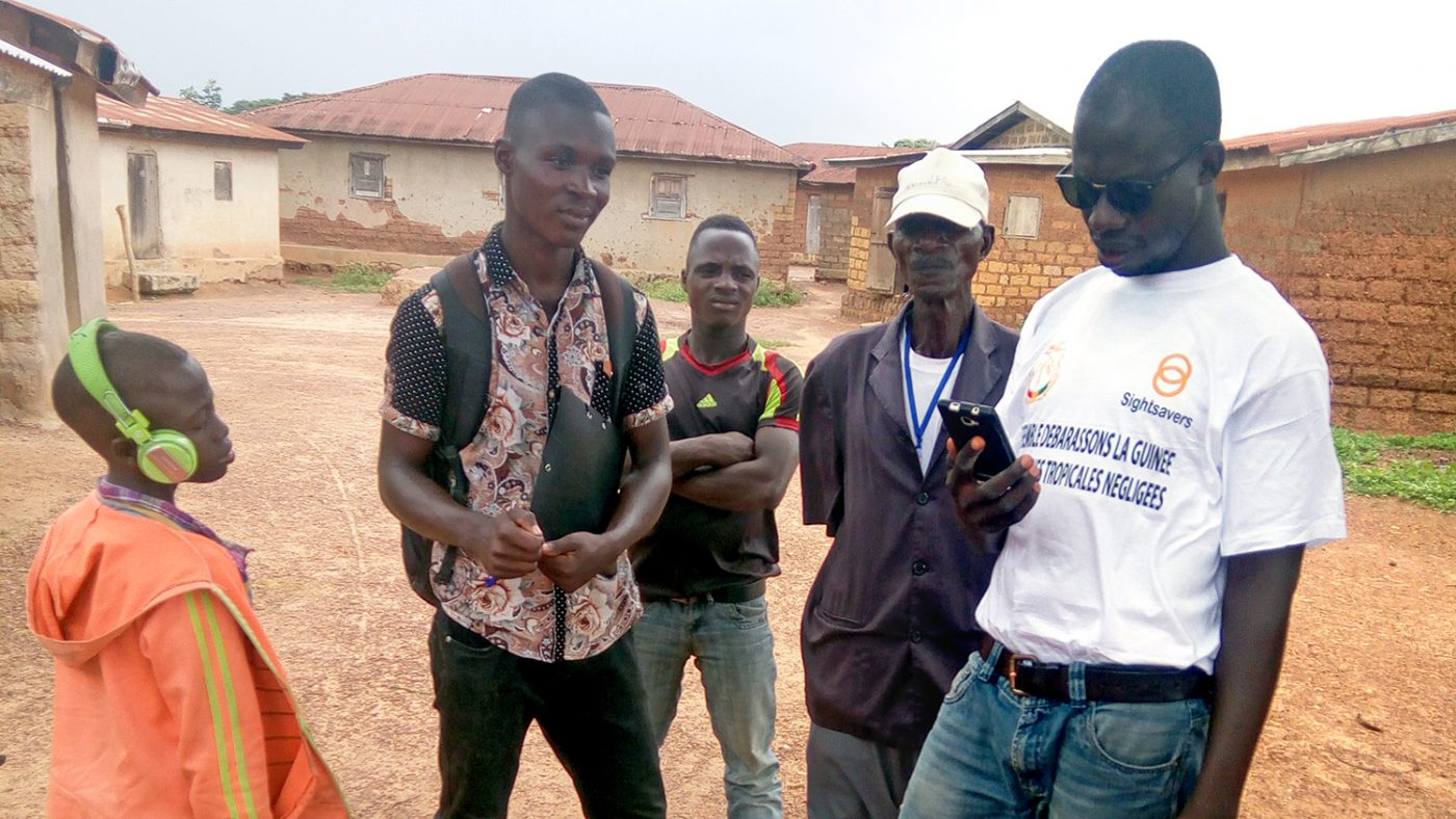 A worker in a Sightsavers t-shirt talks to local villagers and records information on his mobile phone.