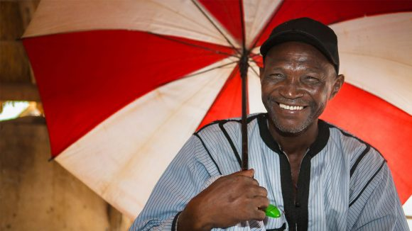 Volunteer community distributor Mamadou Samine from Senegal smiles broadly while holding an umbrella.