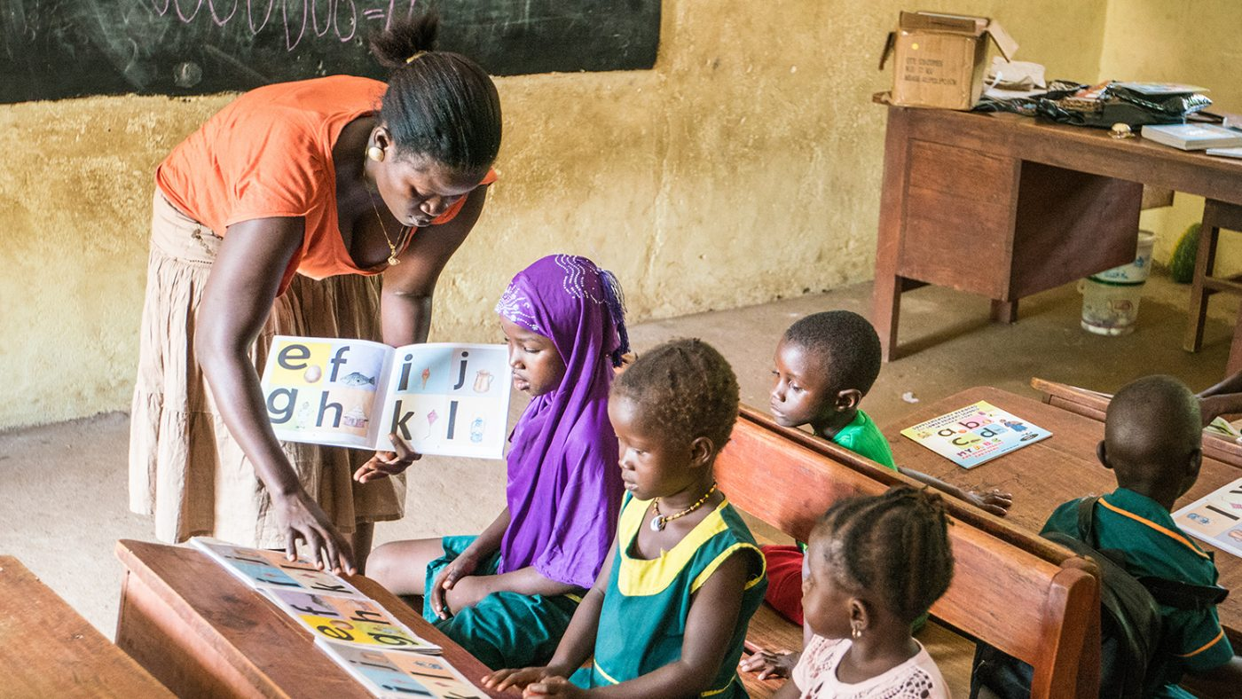 Teach Hassanatu helps pupils in the classroom.