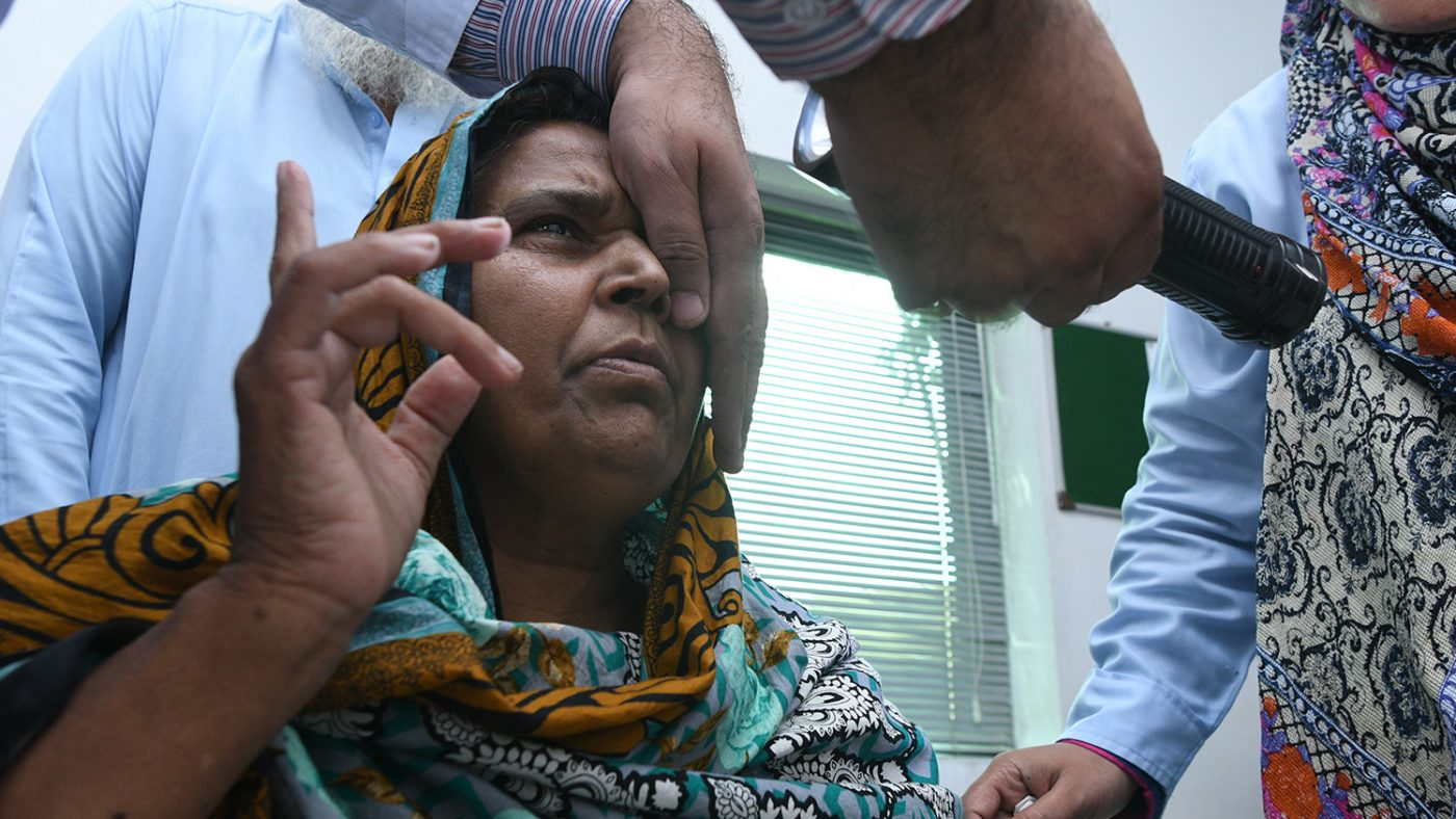 Naheed holds up fingers as the ophthalmologist covers one of her eyes.