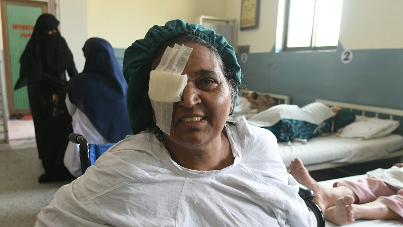 Naheed in a hospital gown with a white bandage over one eye.