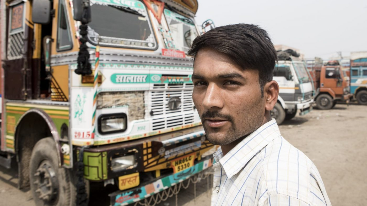 Sandeep Kumar standing in front of his brightly colored truck.