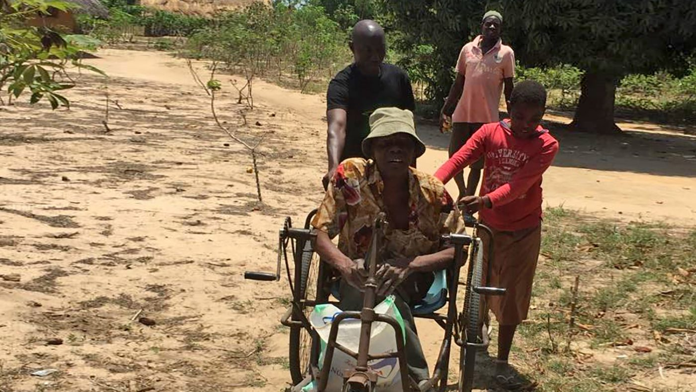 Augusto in his wheelchair accompanied by family members on a trip around his village.