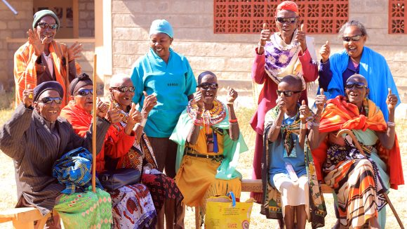 A group of patients in Kenya smile and laugh following their cataract surgery.