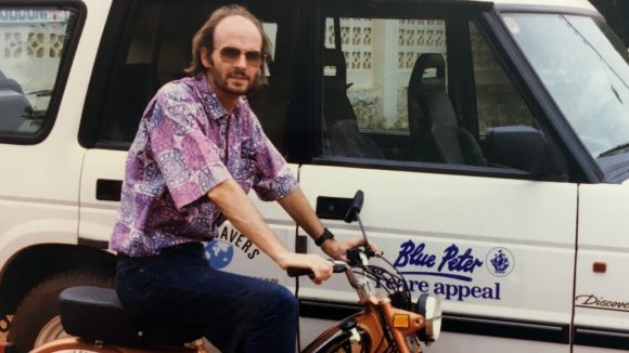 A man on a motorbike next to a truck with a logo that says 'Blue Peter Sight Savers Appeal'.
