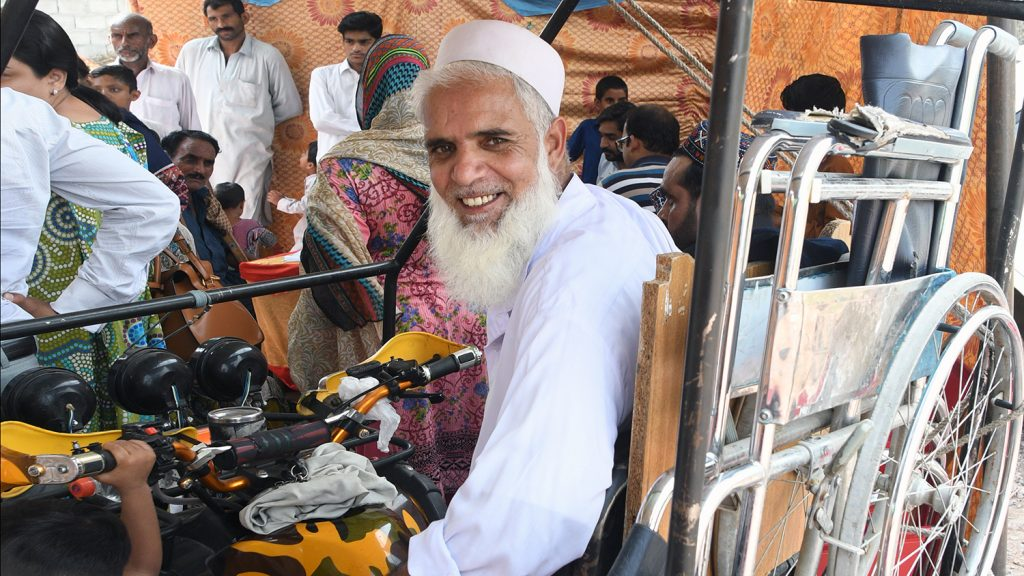 Muhammed smiles as he sits on a small buggy with his wheelchair in a rack behind him.