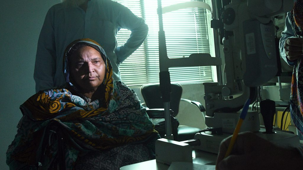 Naheed sitting in a darkened room for an eye test, with light shining on her face.