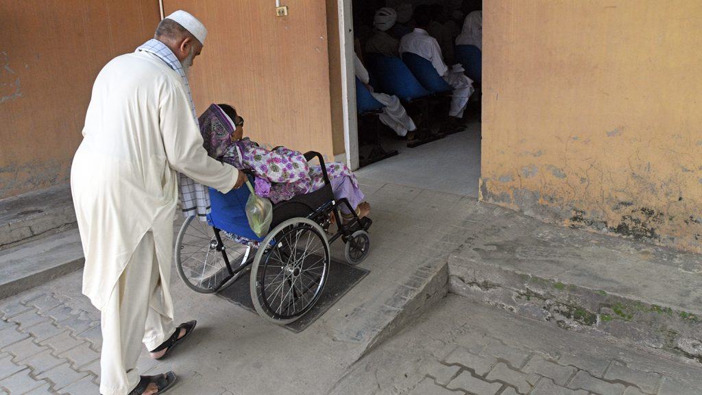 Mahmoud wheels Naheed up a ramp in her wheelchair.