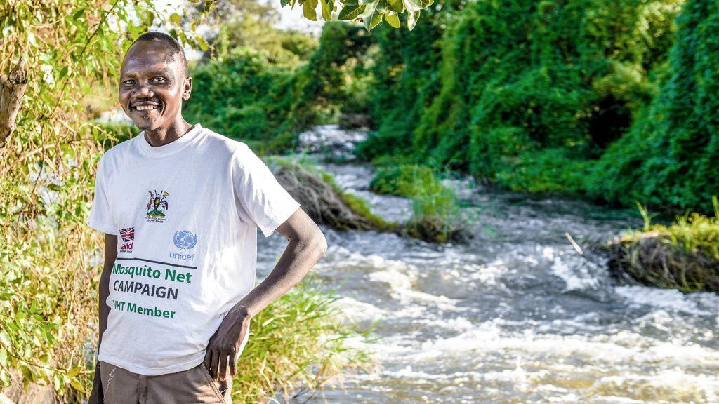 Volunteer Okello Charles stands near a river in Lapaya, Uganda.