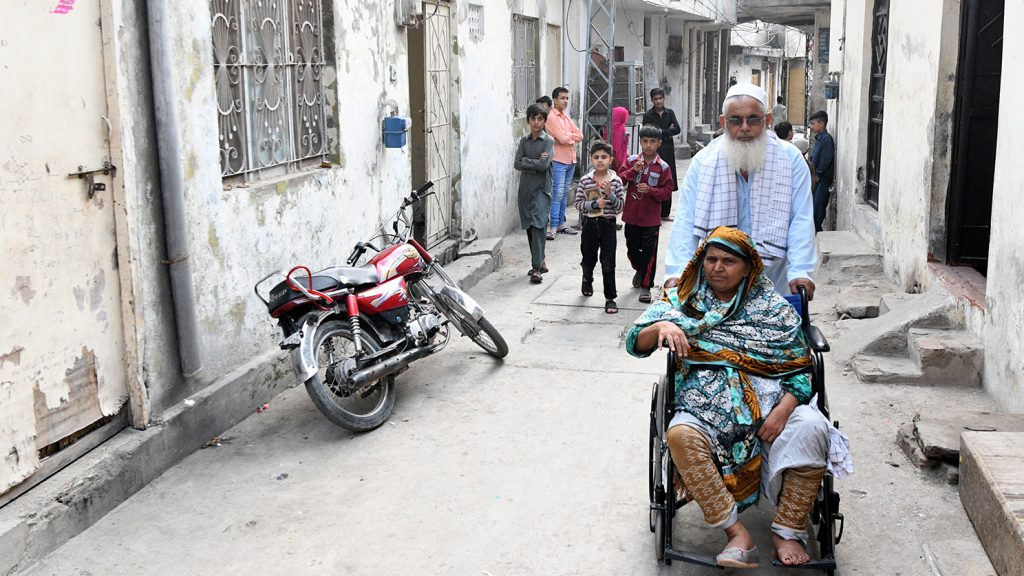 Mahmoud pushes Naheed in her wheelchair outside their home.