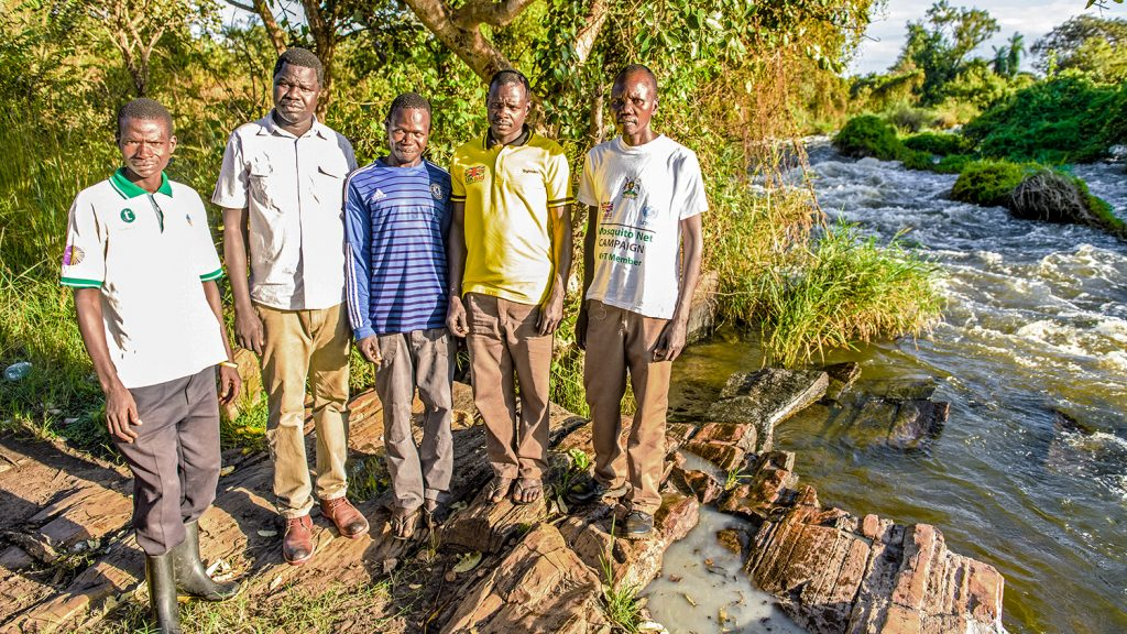 A group of fly catchers stand by the river in Pader, northern Uganda.