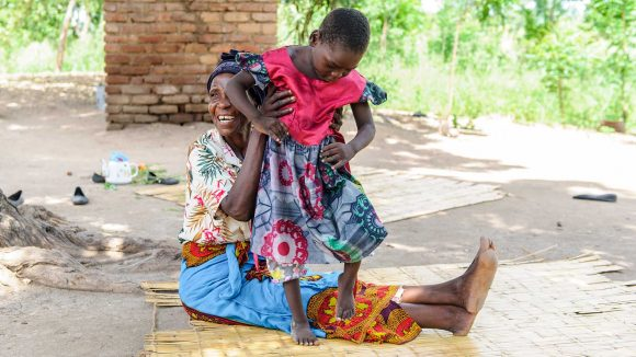 A grandmother is helping her young granddaughter stand.