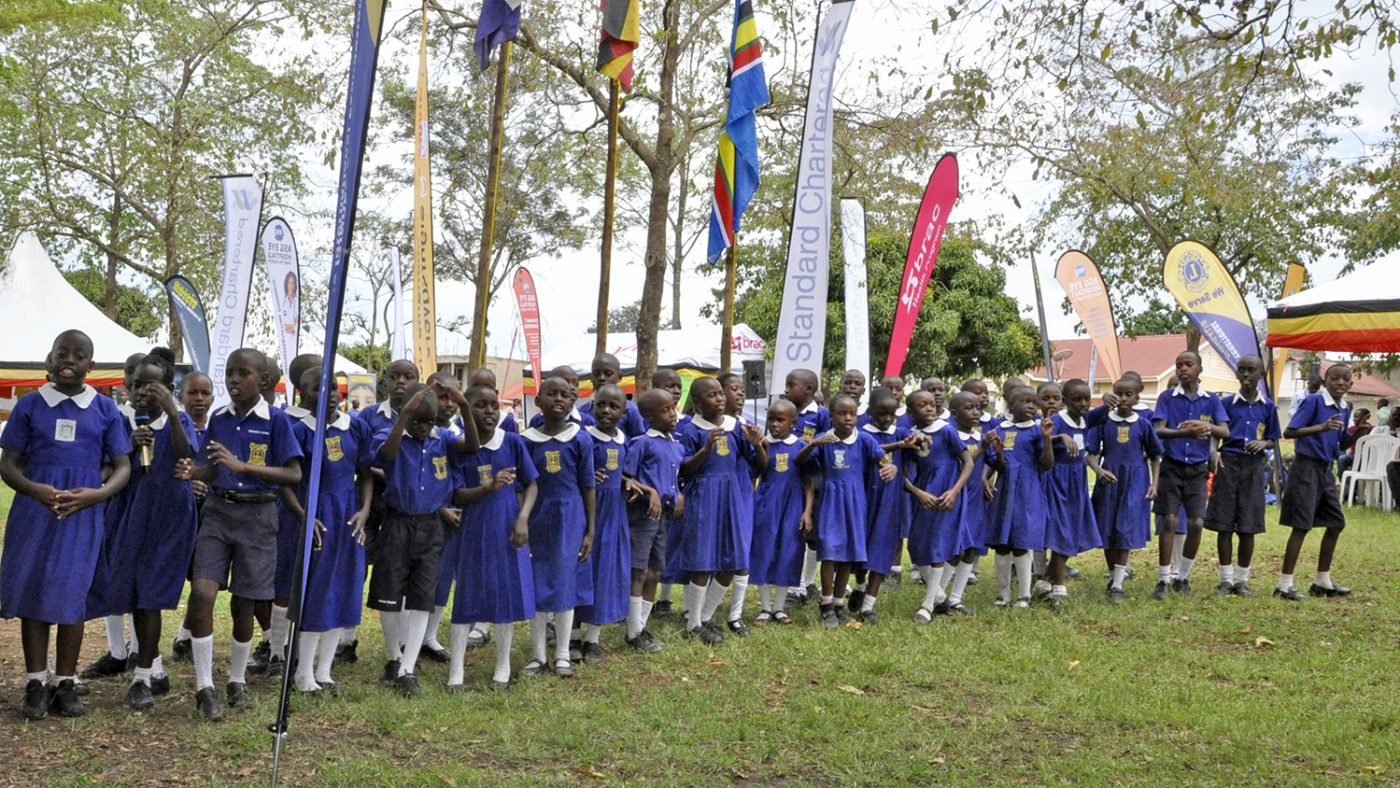 A group of children in blue school uniforms sing songs.