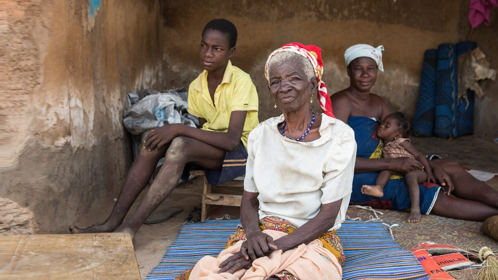 An elderly women sits in front of a mother with young child and a teenage boy.