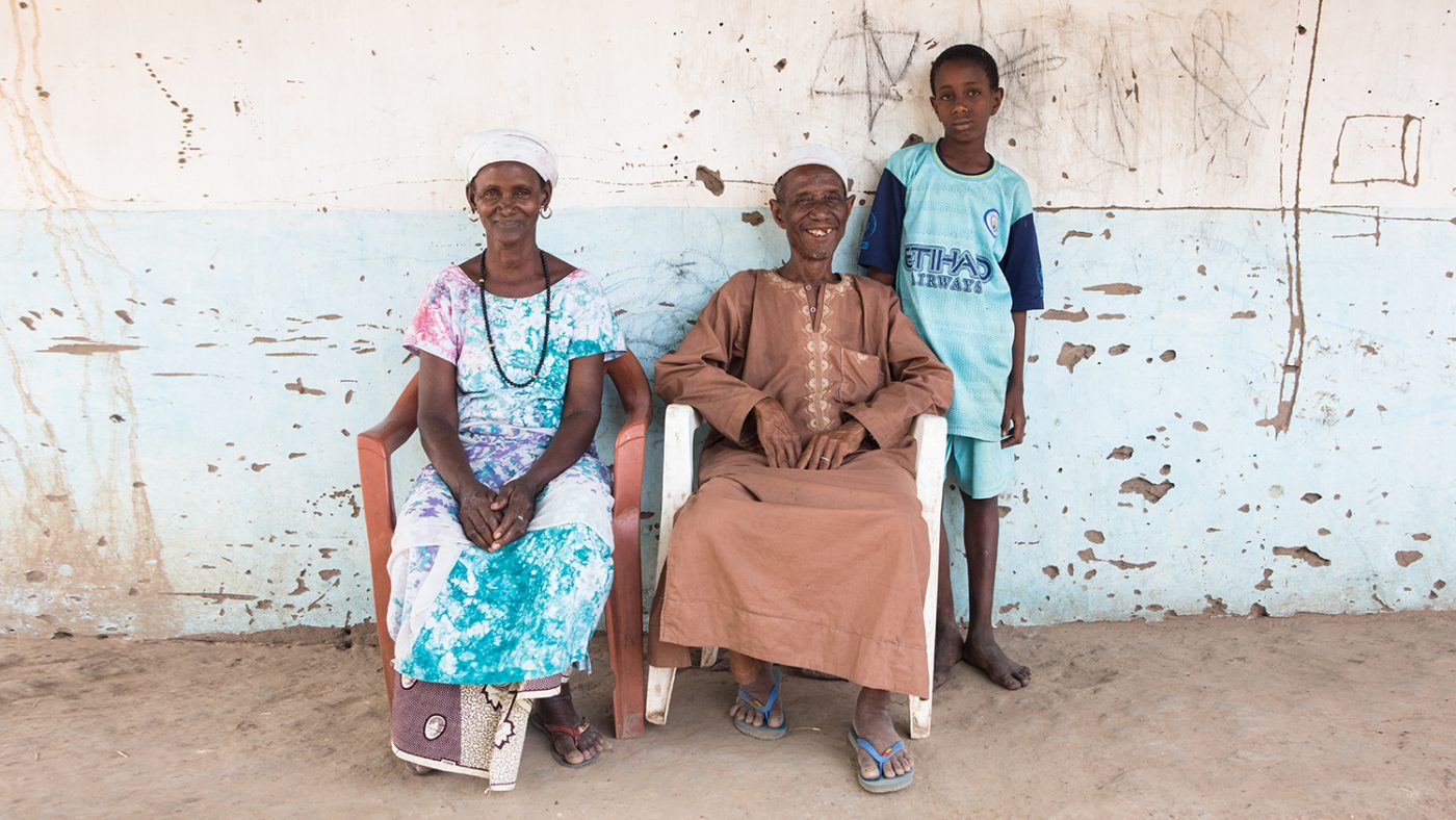 A 12 year old boy stands next to his mum and dad who are sitting.