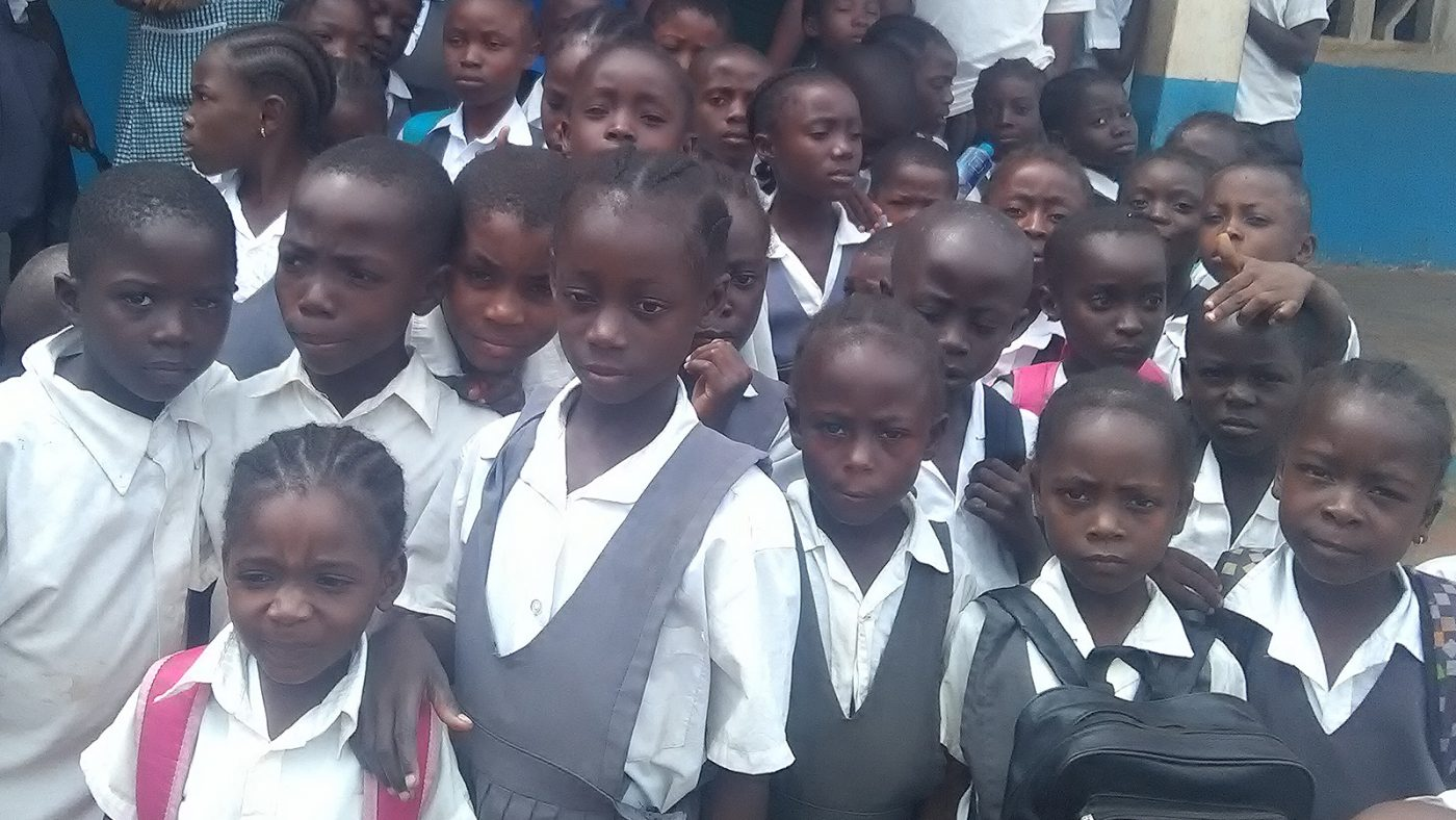 A large group of children standing together outside a building.