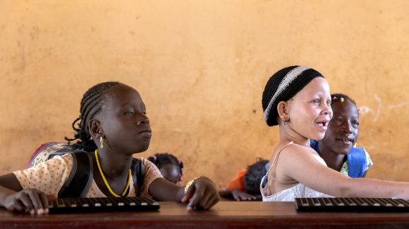 Visually impaired children sitting at a classroom desk.