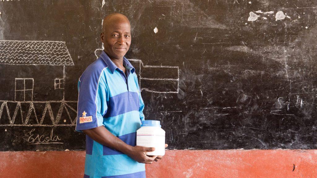 Embessal, a teacher, standing in front of a blackboard in a classroom.