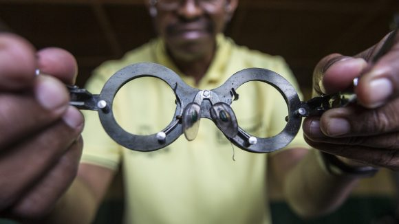 Close up photo of eye testing spectacles being held towards the camera by a man.