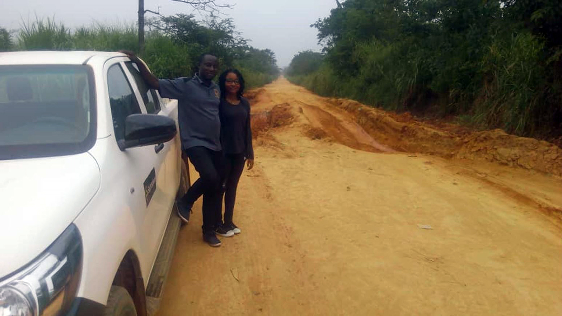 Two staff stand on a dirt road in Guinea.