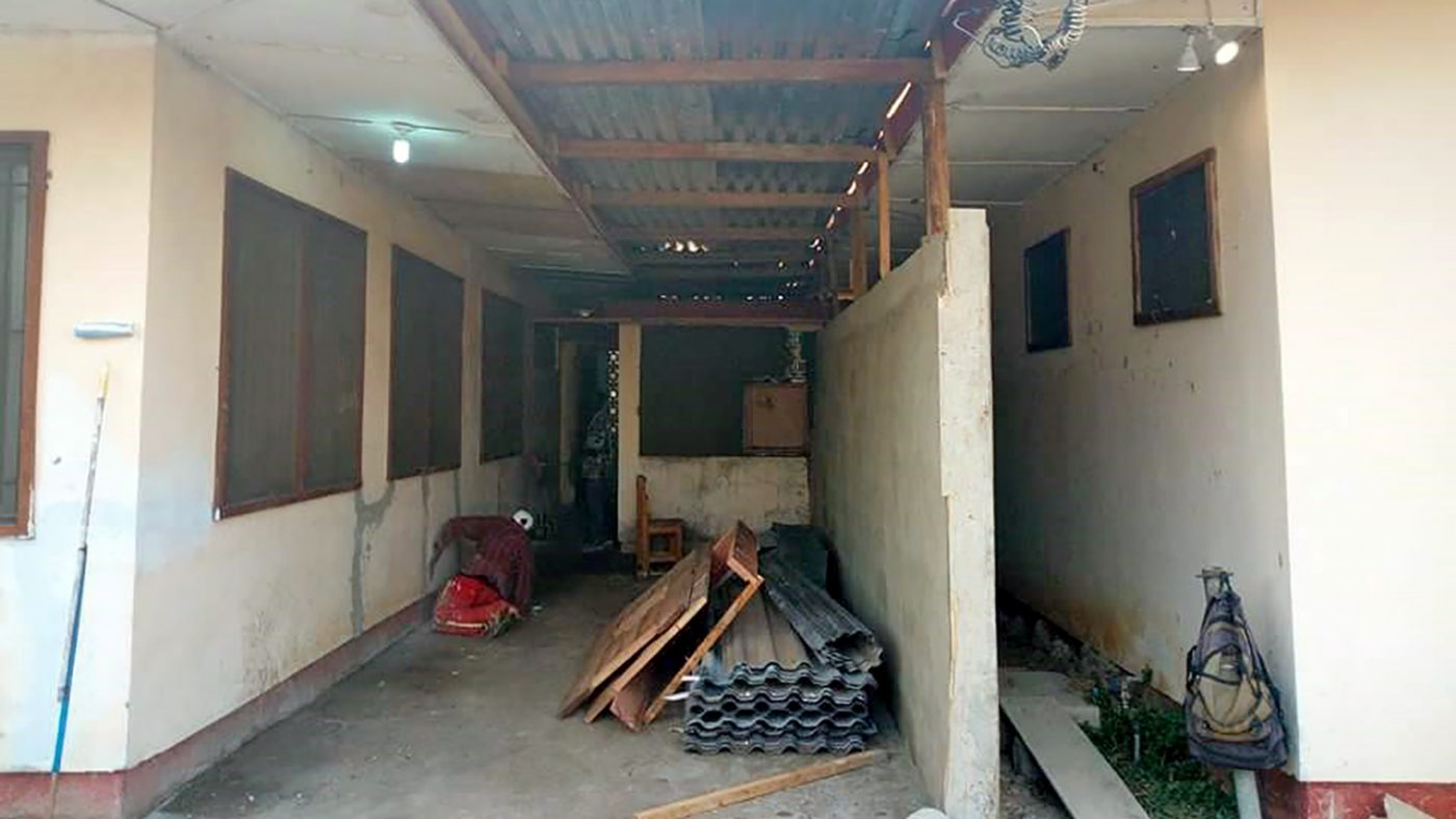 The clinic in Liberia during renovation work: the rooms are missing their ceilings and there are building supplies scattered about.