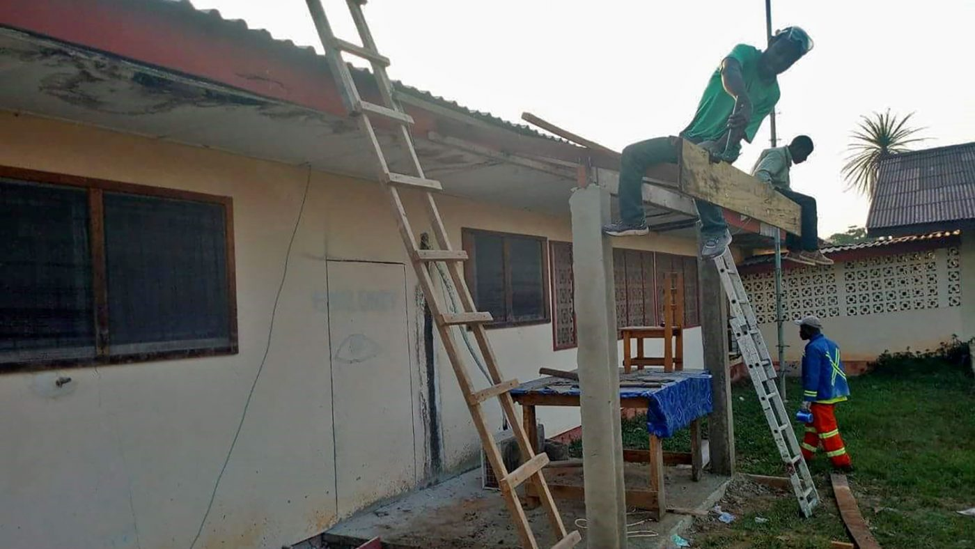 Workmen climb ladders outside the clinic as they work on the roof.