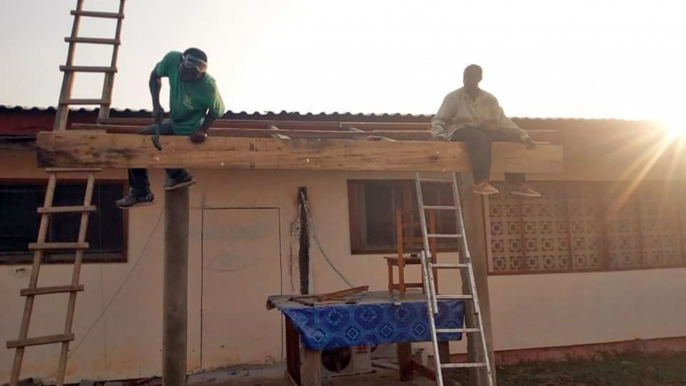 Workmen sit on the roof of the clinic during the renovations.