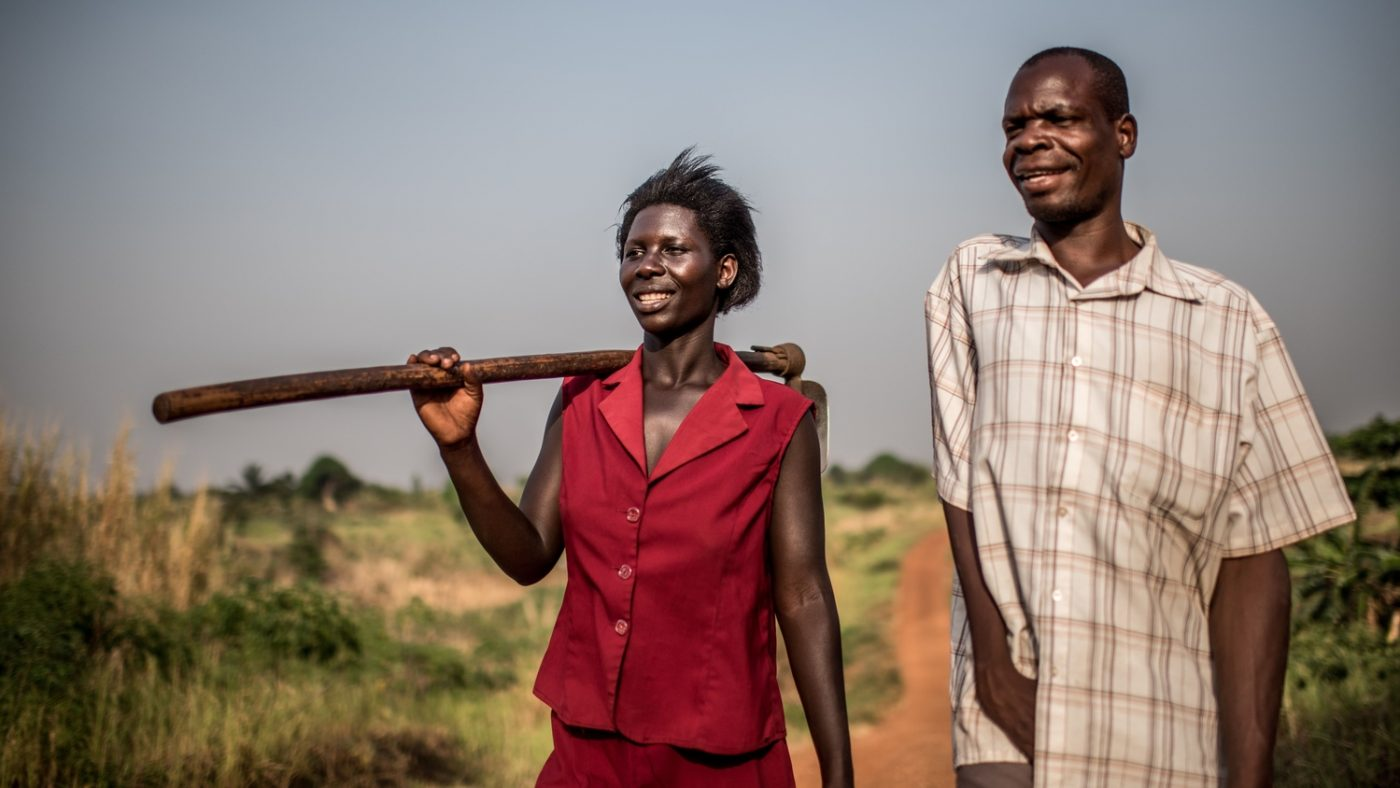A man and woman walk together on a farm. The woman is carrying a farm implement and the man has a physical disability affecting his arm.