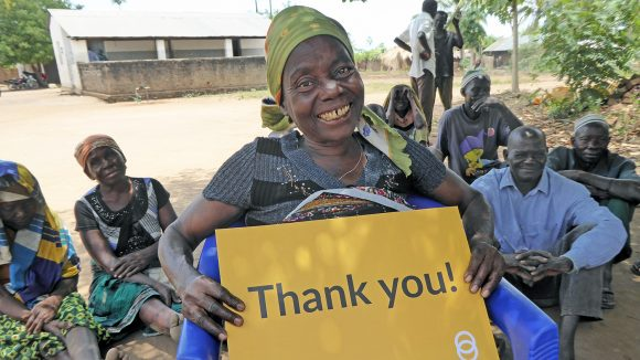 A lady in Mozambique holding a yellow sign saying 'thank you'.