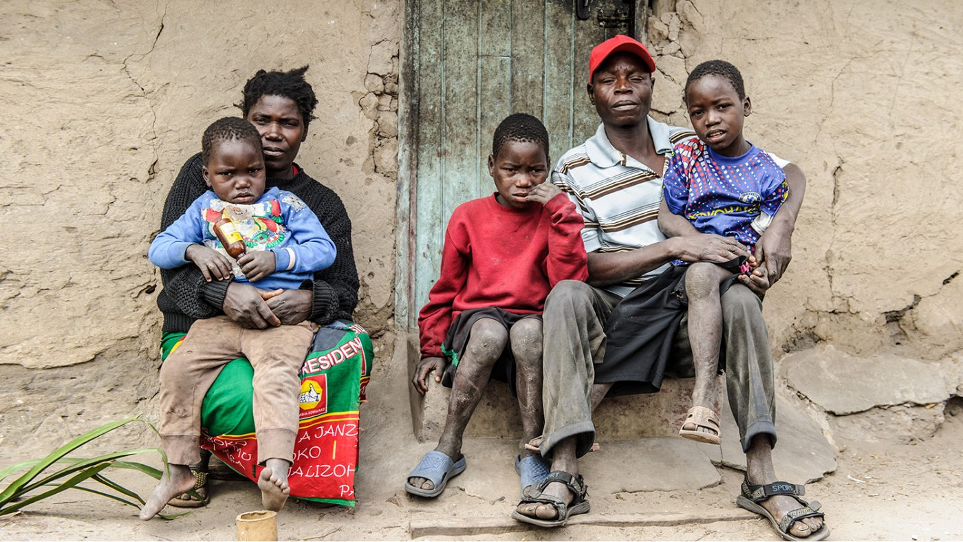 Mwiza and his family sitting outside their home.