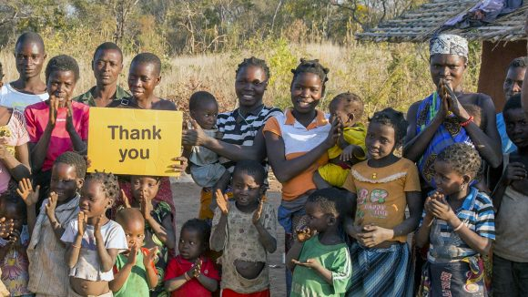 In Mozambique, a group of villagers smile and hold up a yellow sign saying 'thank you'.
