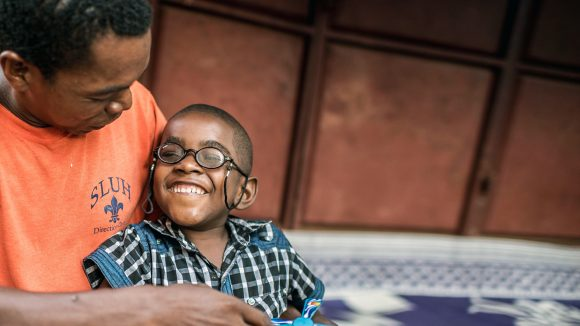 Five-year-old Saidi smiles while sitting on his father's lap following cataract surgery.