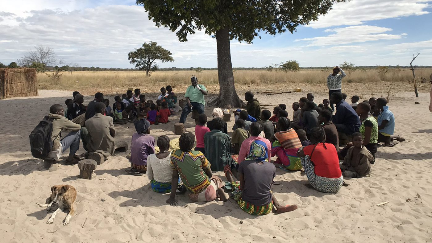 A group of villagers gather under a tree to listen to an eye health worker talk.